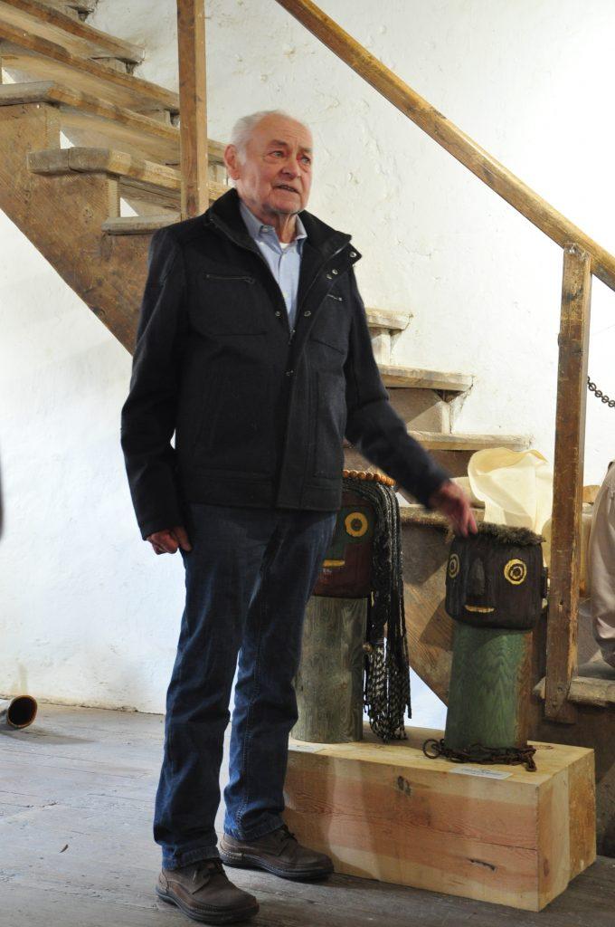 H.Kröger erklärt die Entstehung der Köpfe der Totempfähle,welche bis zu 2 meter hoch sind und in seinem Garten stehen